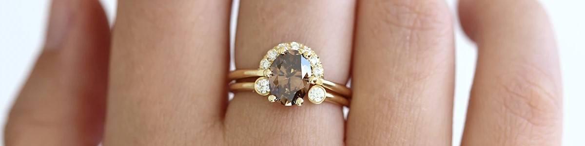imagen de anillo de diamante marrón sobre mano