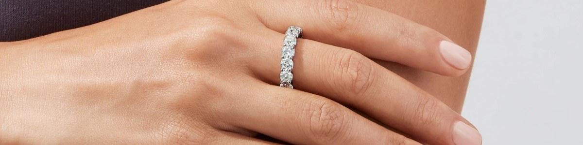 mano con anillo con varios diamantes redondos